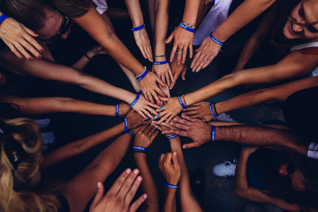 A group of people put their hands into the center prepping for a group cheer