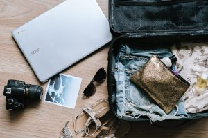 Laptop, camera, shoes, sunglasses & clothes in a suitcase